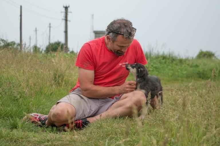 Gut Aiderbichl Tierpfleger mit gerettetem Hund aus Rumänien